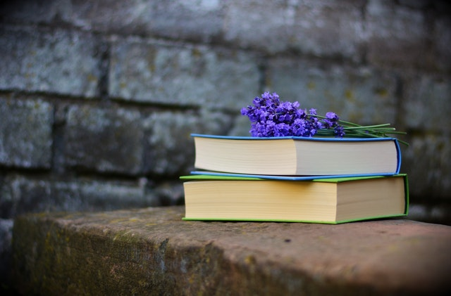 Two Books Sitting on Stone with Lilacs on Top